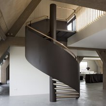 A spiral staircase with a handrail of copper in an attic with wooden beams and a concrete floor and wall.