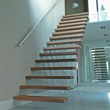 Floating wooden treads with a stainless steel handrail in a hall with high plinths, spotlighting and a mirror wall.