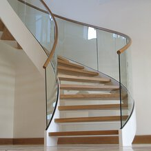 A reflection in the glass balustrade of a winding staircase in front of a stucco wall with wooden plinths.