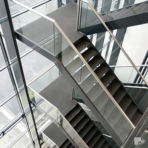 Different black stairs on top of each other with glass railings and stainless steel handrails, against a glass wall.