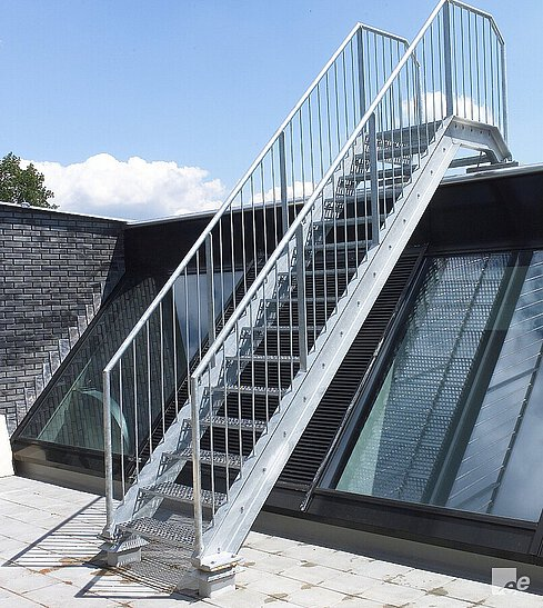 A galvanised steel emergency staircase on a roof terrace by which skylights and a brick wall are visible.