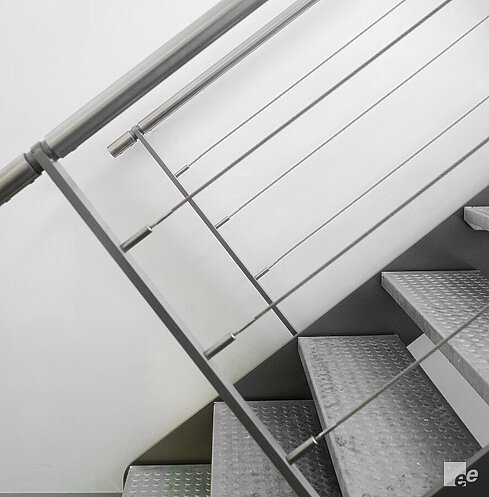 A functional steel staircase with galvanised checker plate treads and a balustrade with tension wires in front of a white stucco wall.