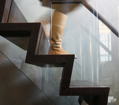 A wooden spiral staircase with wooden handrail walked on by a woman with brown boots.