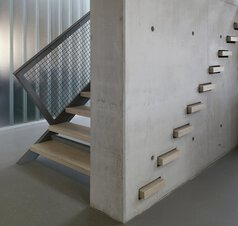 A staircase with wooden treads and a balustrade with stainless steel net between a concrete wall and metal railings.