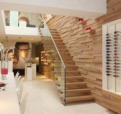 Sunglasses, a poster, a ceiling with lighting and along the wooden wall a floating staircase.