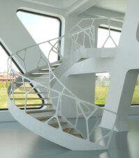 A winding staircase with balustrades with cell motif in a hall with cast floor, open wall and triangular windows.