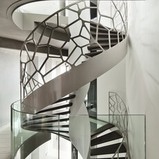 A stucco ceiling around a stairwell with a spiral staircase with stainless steel balustrade system inside and glass balustrades in front.