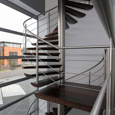 A wooden floating spiral staircase with a stainless steel balustrade with railing and intermediate landing. Through the glass façade, the parking spaces are visible.