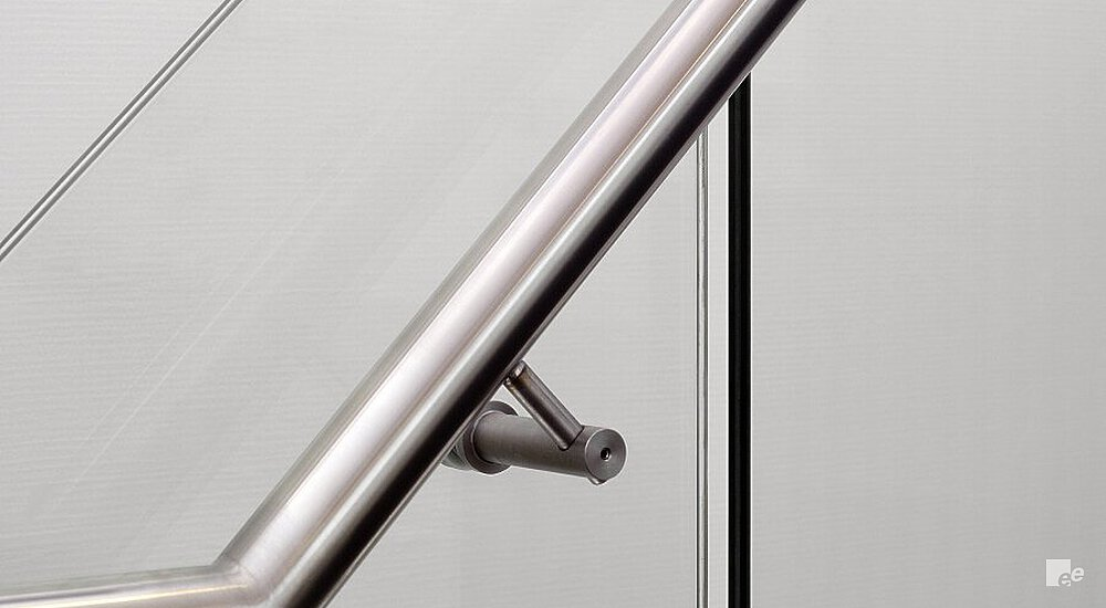 A stainless steel handrail, secured to a glass balustrade with a white stucco wall in the background.