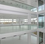 A hall with white concrete pillars, white stucco walls, glass doors and glass balustrades with handrails.