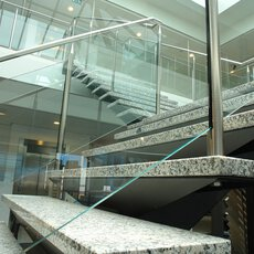 A hall with a lift, ceiling lighting and a staircase with marble treads, glass balustrades and stainless steel balusters.