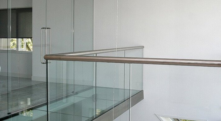 A loft with a glass floor and glass doors. Further, the rolling blinds and hanging ceiling spotlights are visible.