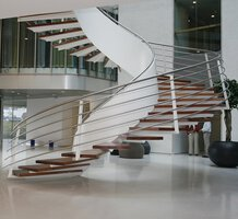 Floating winding staircase with wooden treads in a large reception hall with white cast floor and indoor plant.