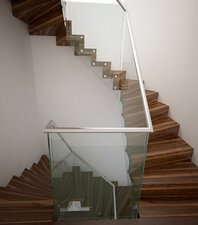 Two quarter-landing stairs with spacers, wooden treads and glass balustrades in a hall with white stucco walls.