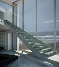 A flight of stairs in front of a glass façade with a view of the sea, in a hall with marble floor.