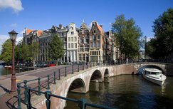 The inner city of Amsterdam, with façade buildings and trees. The photo also shows a canal boat, canal and bridge.