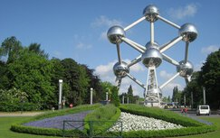 The Atomium in Heizel Park in Brussels, surrounded by trees and flowers. Traffic is also driving by.