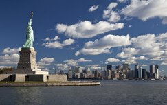 The Statue of Liberty in New York Bay in the United States, with a view of the skyline and clouds.
