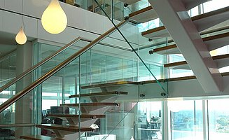 The landing staircase in the building of RBS. The staircase pillar, hanging lamp and glass façade are also visible.