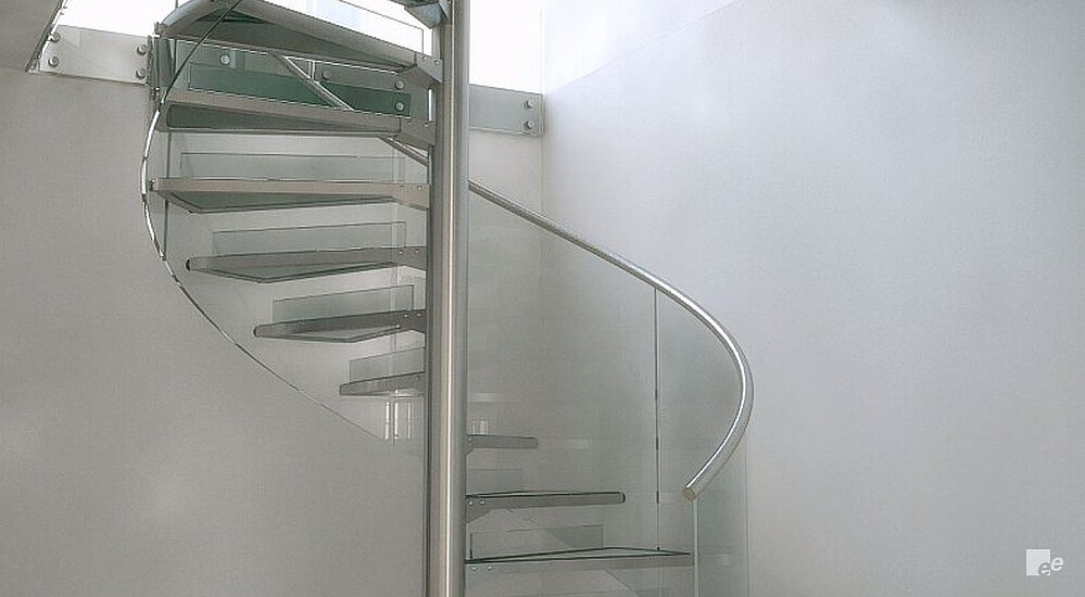 A spiral staircase with floating treads, balustrade and glass canopy between white stucco walls above a natural stone floor.