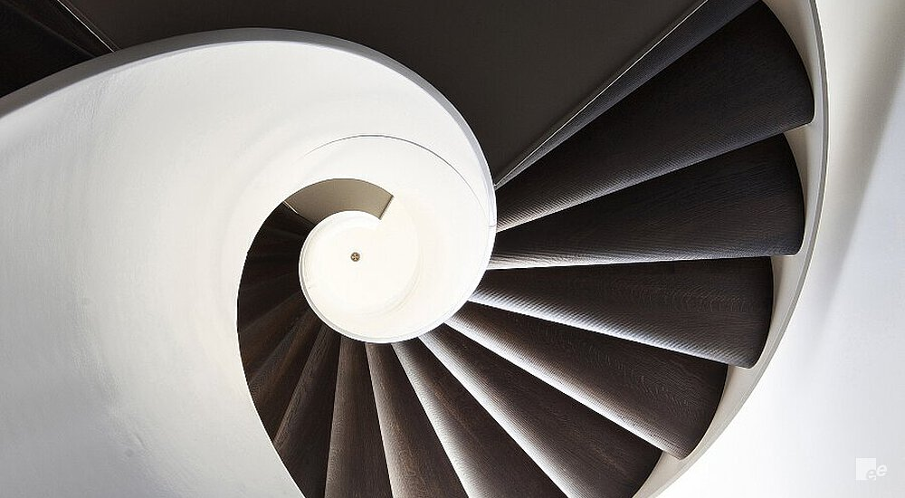 The underside of a spiral staircase with walnut wood treads, along a white stucco wall in an apartment.