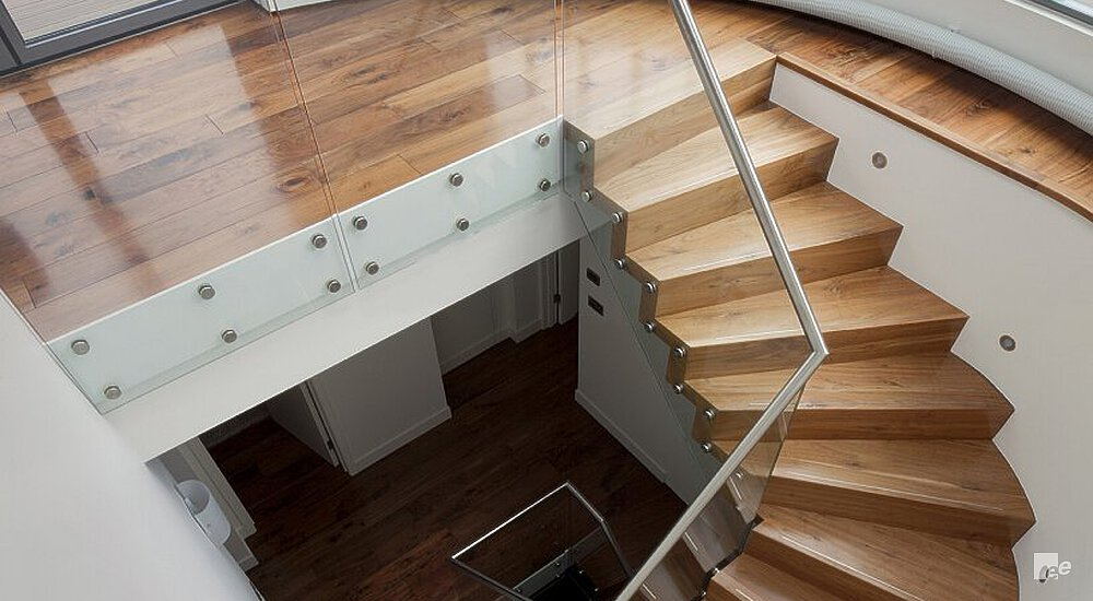 A winding staircase next to glass balustrades and a wall with wall lighting. Above the staircase lies a parquet floor.