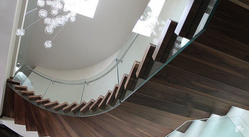 Hanging lamps, a white stucco wall and a floating staircase with walnut wood treads and a glass balustrade.