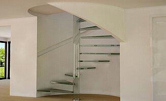 A glass pivot and glass treads above a parquet floor in a stairwell with white stucco walls.
