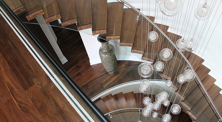 A floating staircase with walnut wood treads turns around hanging lamps and next to a natural stone vase.