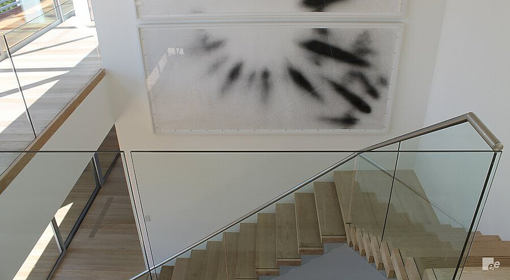 Two frames with black shapes as illustrations, in a space with a staircase, parquet floor and balustrade.