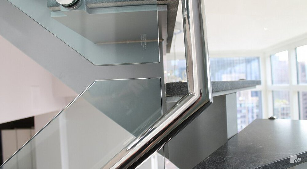 Donker granieten traptreden, een spiegelglans RVS trapleuning, een glazen balustrade en zicht op Manhattan.	Dark granite staircase treads, a mirror polished stainless steel staircase rail, a glass balustrade and view of Manhattan.