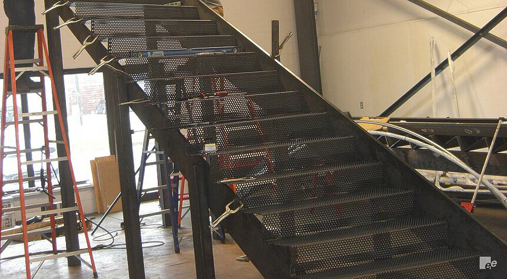 A person on a stepladder by a staircase with steel treads, by a wall with steel frame.