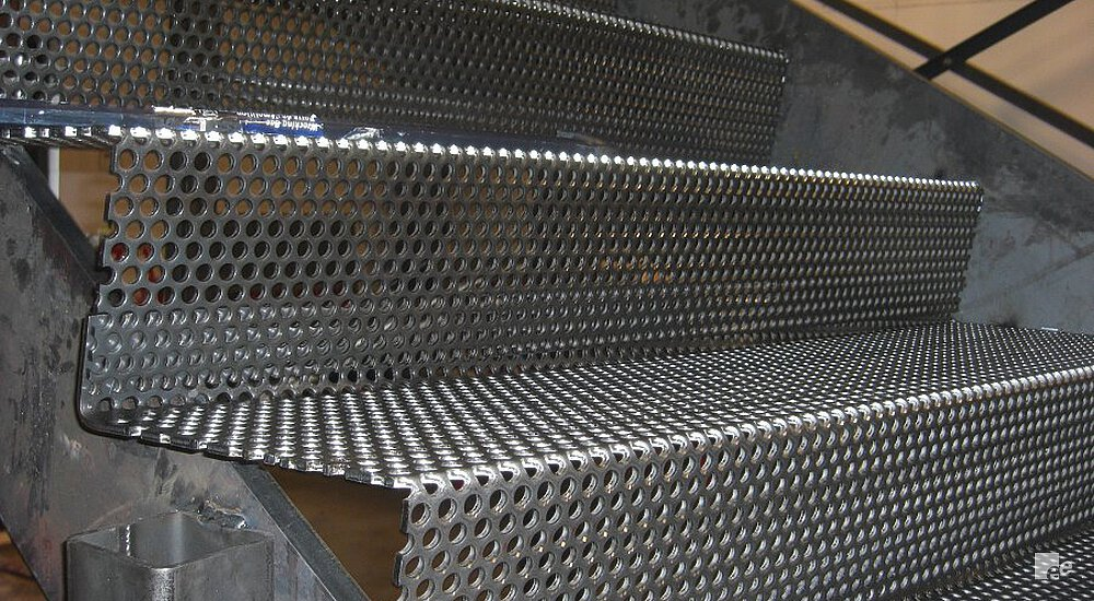 Staircase treads of perforated steel in a workplace, with a tool on one of the treads.