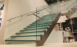 A staircase with glass treads and glass balustrade in the Le Chateau shopping centre in Calgary.