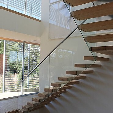 A floating staircase with oaken treads and glass balustrades, in a hall with windows with awning.