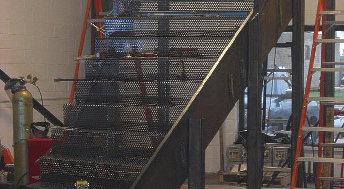 A flight of stairs with treads of perforated steel, between two stepladders in the EeStairs workplace.