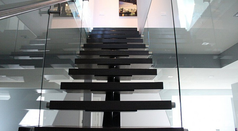 ... A Spiral Staircase With Dark Stained Oaken Treads Leads To A White  Stucco Wall With An ...