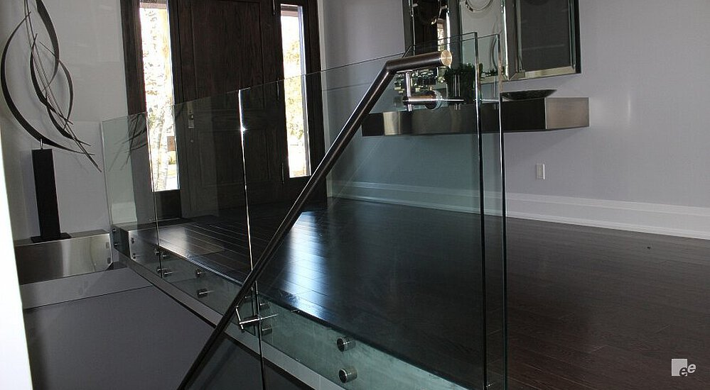 A dark stained oaken floor, glass balustrade and three frames. Behind that is a double door with glass.