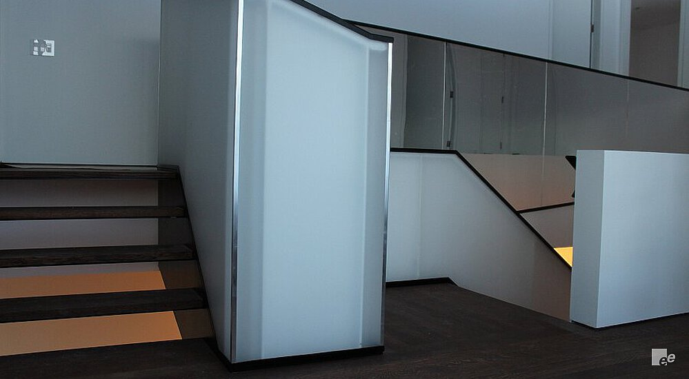 A balustrade with panels of matte acrylic, a dark stained oaken floor and an oaken staircase.