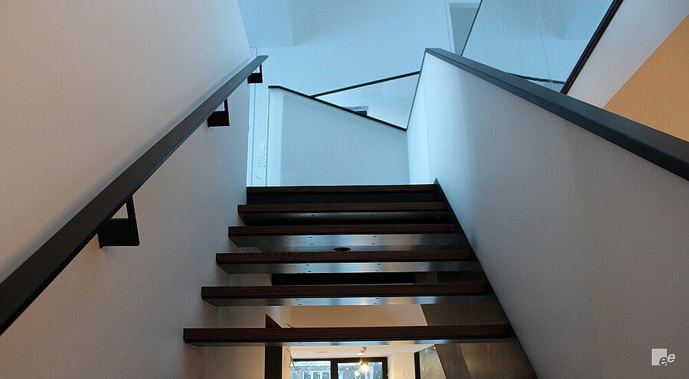 An open staircase with oaken treads, next to a white stucco wall and balustrade with wooden rail.