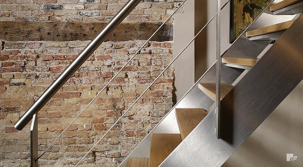... A Brushed Stainless Steel Staircase With Wooden Treads And Tension  Wires In Front Of A Rough