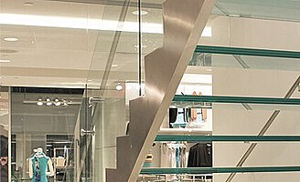 A stainless steel open flight of stairs with glass treads and balustrades in a shop with clothing racks and a tailor's mannequin.