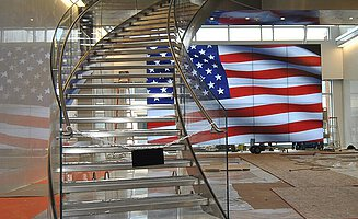 An open staircase with glass balustrades, in front of a glass façade and a flag of the United States.