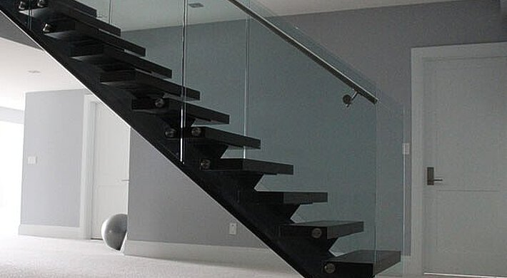 A straight staircase, carpet floor and flat door in the offices of a contractor in Toronto in Canada.