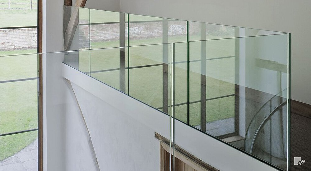 A glass balustrade, window frame with a view of grass, wooden door and oaken beams in a farm shed.