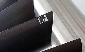 A stainless steel centre column with curved wooden treads and a sticker with an EeStairs logo.