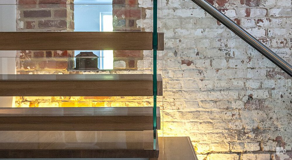 A part of an oaken landing staircase, in front of a brick wall and with a glass balustrade.