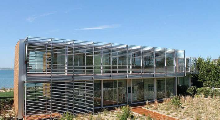 A summer residence with glass walls in Long Island, against a clear blue sky. In front of that lies a garden with vegetation.