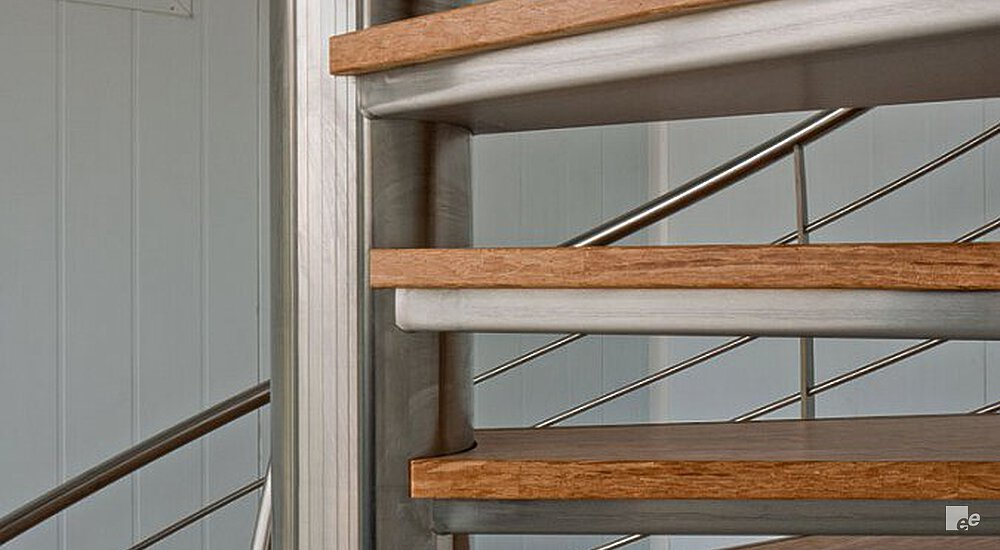 Spiral stairs with wooden steps, with a stainless steel spindle and stainless steel handrails with mid-rails.