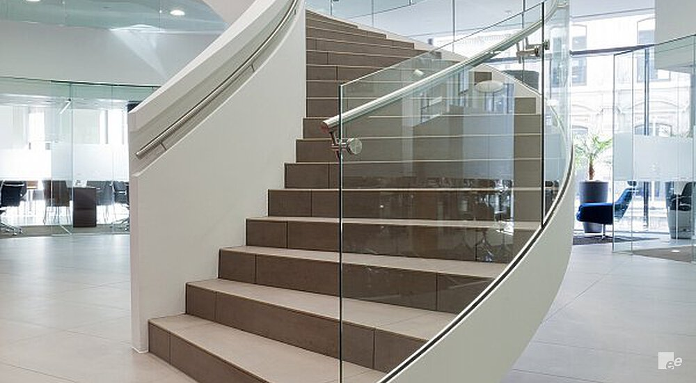 A winding staircase with a glass and closed balustrade, above a cast floor in the offices of an insurer.
